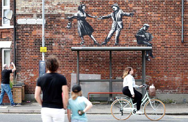 Alcune persone si fermano a guardare un'opera d'arte che sarebbe stata creata da Banksy a Great Yarmouth, in Gran Bretagna, l'8 agosto 2021. - Sputnik Italia