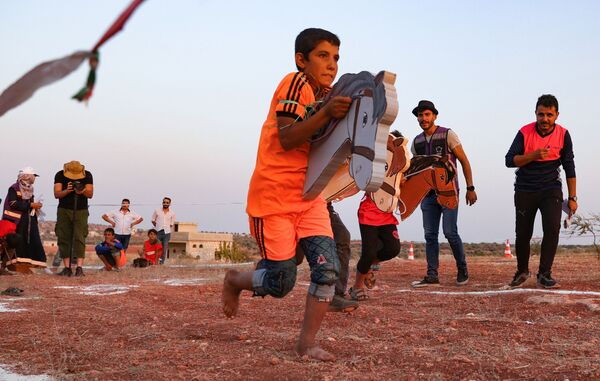 """Un bambino siriano sfollato corre con un giocattolo a forma di cavallo, durante le cosiddette """"Olimpiadi del campo 2020"""", organizzate dai ragazzi dei diversi campi profughi siriani della regione di Idlib, il 7 agosto 2021. La regione di Idlib ospita quasi tre milioni di rifiugiati.  - Sputnik Italia"""