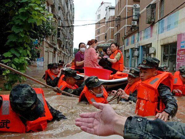 Alcuni agenti di polizia aiutano nelle operazioni di evacuazione dei residenti bloccati dalle inondazioni, a seguito delle piogge torrenziali nella città di Suizhou, provincia di Hubei, Cina, il 12 agosto 2021. - Sputnik Italia
