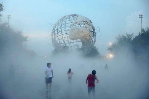 Alcune persone giocano nel giardino annebbiato, nel Flushing Meadows-Corona Park, mentre un'ondata di caldo colpisce la regione, New York City, Stati Uniti, 11 agosto 2021. - Sputnik Italia