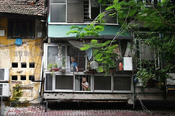 I bambini guardano dalle finestre le strade vuote di Hanoi, l'11 agosto 2021, dopo l'imposizione, da parte del governo, di un nuovo lockdown di due settimane per trattenere la diffusione del Covid-19. - Sputnik Italia