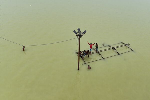 Alcuni ragazzi giocano in cima a una struttura sommersa, su una delle rive allagate del fiume Gange ad Allahabad, India, l'8 agosto 2021. - Sputnik Italia