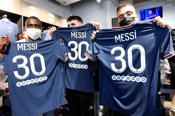 I tifosi fanno le foto con le maglie con il numero 30 del calciatore argentino, che hanno appena acquistato nel negozio del club negli Champs Elysees a Parigi l'11 agosto 2021. Messi vestirà la maglia numero 30 come al debutto con il Barcellona del 16 ottobre 2004. - Sputnik Italia