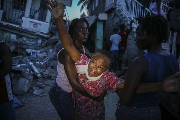 Una donna piange dopo che il corpo di sua figlia di 7 anni è stato recuperato dalle macerie della loro casa distrutta dal terremoto. - Sputnik Italia