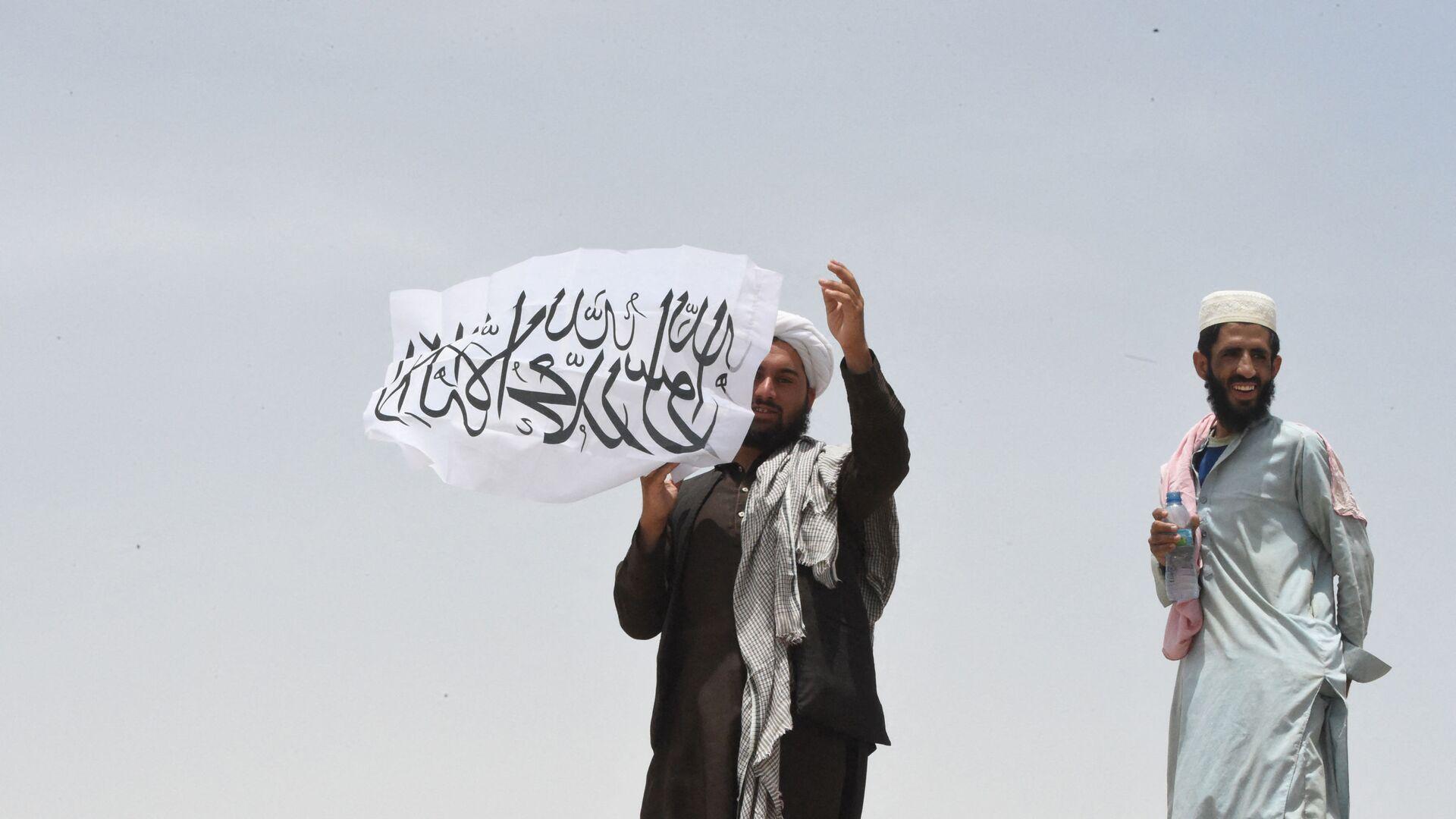 Uomo con la bandiera dei Talebani - Sputnik Italia, 1920, 23.08.2021