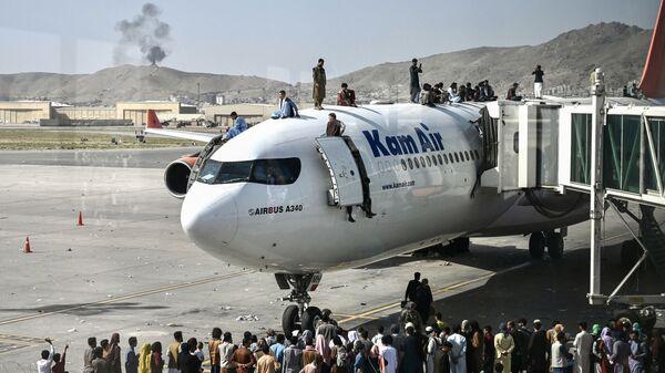 Афганцы забираются на самолет в аэропорту после вступления талибов в Кабул - Sputnik Italia