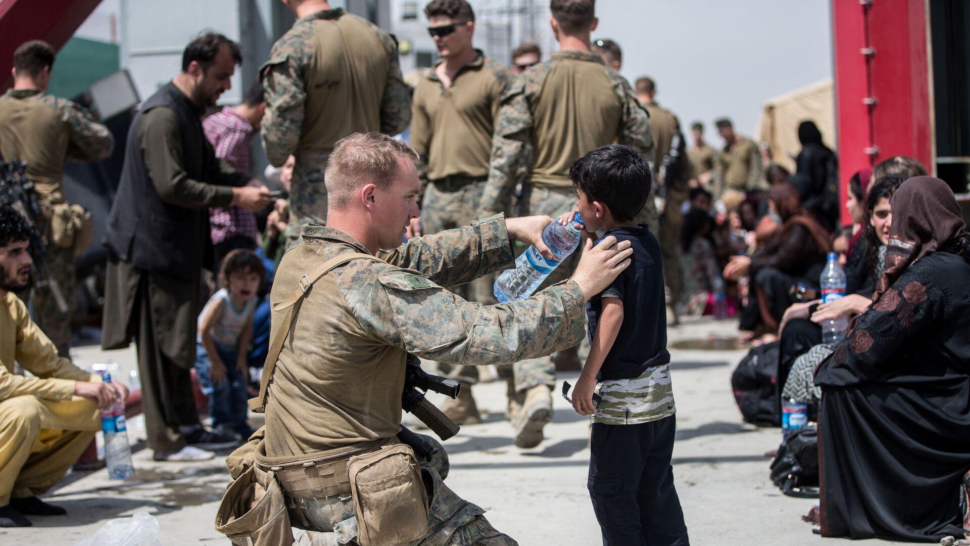 Американский солдат дает воду ребенку в аэропорту Кабула  - Sputnik Italia, 1920, 28.08.2021