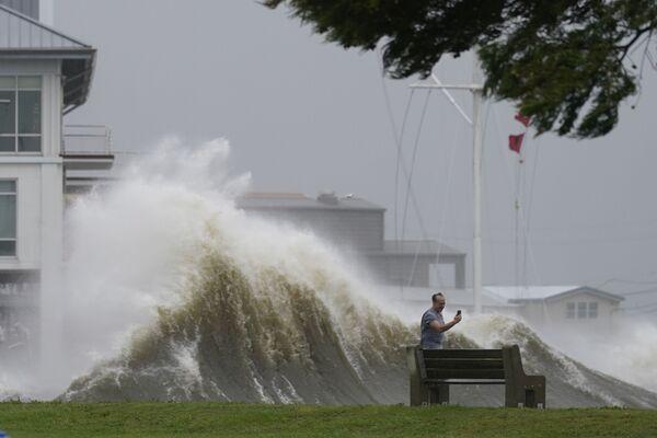 Un uomo fotografa i cavalloni lungo la riva del lago Pontchartrain mentre si avvicina l'uragano Ida, domenica 29 agosto 2021, a New Orleans. - Sputnik Italia