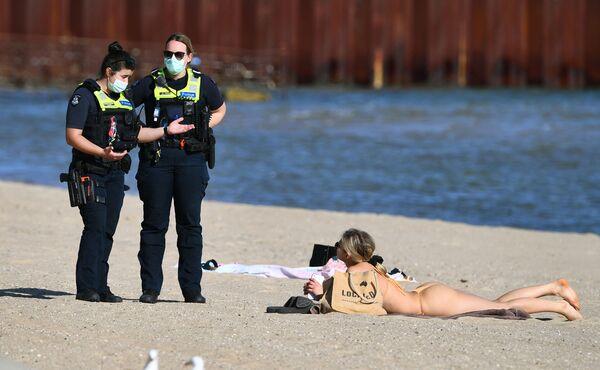 La polizia parla con una donna che si gode il sole a St. Kilda Beach a Melbourne, il 2 settembre 2021, mentre la città rimane bloccata per la variante Delta del coronavirus. - Sputnik Italia