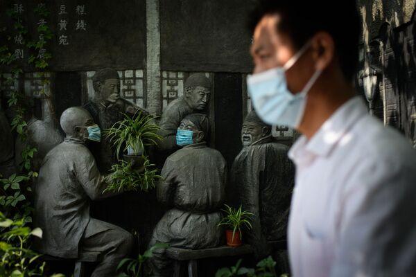 Un uomo passa davanti a una scultura coperta di mascherine, davanti a un ristorante a Pechino, il 29 agosto 2021. - Sputnik Italia