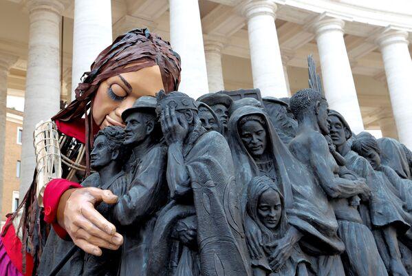 """Durante la sua visita in Vaticano Amal si è fermata davanti la statua """"Angels Unawares""""(angeli inconsapevoli), raffigurante migranti e rifugiati da luoghi ed epoche diversi, tutti sulla stessa barca. - Sputnik Italia"""