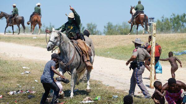 Пограничный патруль США на лошади пытается помешать гаитянскому мигранту войти в лагерь на берегу Рио-Гранде - Sputnik Italia