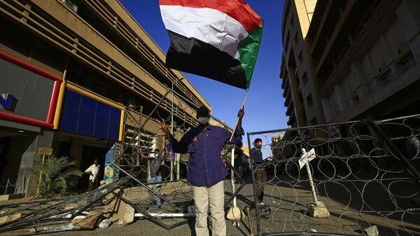 Суданец машет флагом своей страны в столице Судана Хартуме - Sputnik Italia