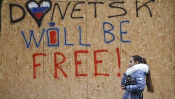 Женщина идет мимо надписи Donetsk will be free в Донецке - Sputnik Italia
