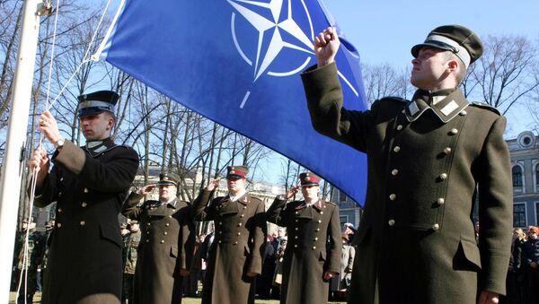 Militari lettoni e la bandiera della Nato - Sputnik Italia