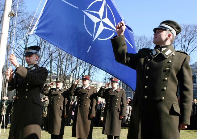 Latvian officers stand guard during the NATO flag rising ceremony in front of the Presidents castle in Riga