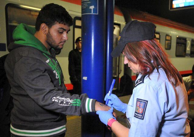 Un agente di polizia ceco marchia un migrante