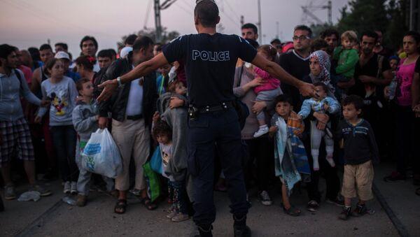 Poliziotto tra migranti in Grecia al confine con la Macedonia - Sputnik Italia