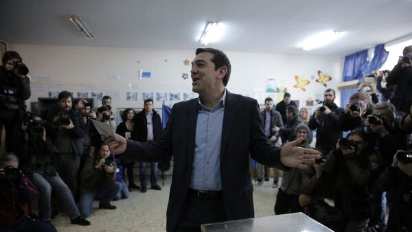 Alexis Tsipras, leader of Greece's Syriza left-wing main opposition party surrounded by photographers reacts as he casts his vote at a polling station in Athens, Sunday, Jan. 25, 2015 - Sputnik Italia