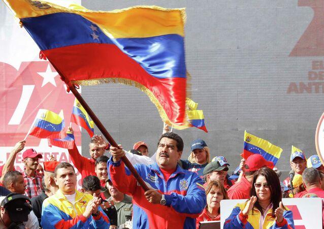 Nicolas Maduro, presidente del Venezuela, sventola una bandiera del suo paese