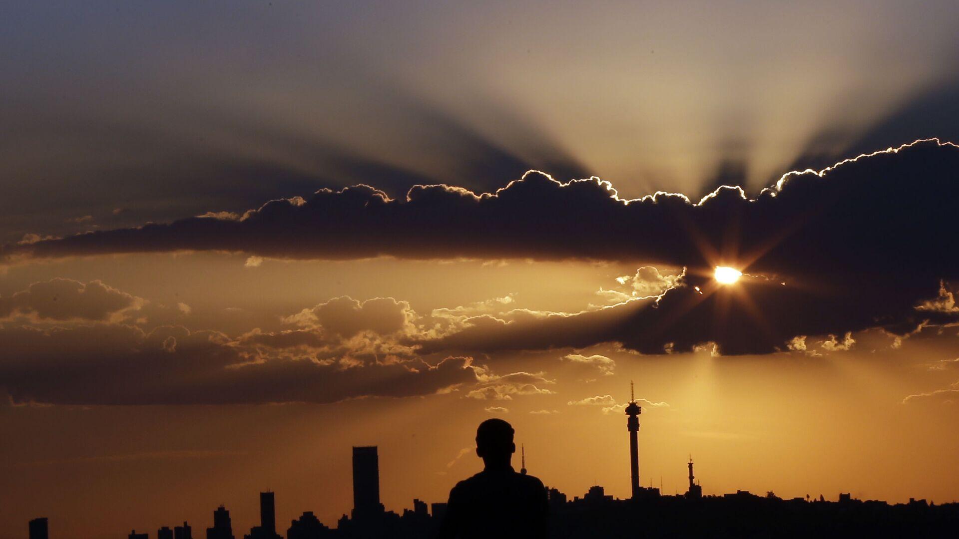 Человек смотрит закат в Йоханнесбурге - Sputnik Italia, 1920, 12.07.2021