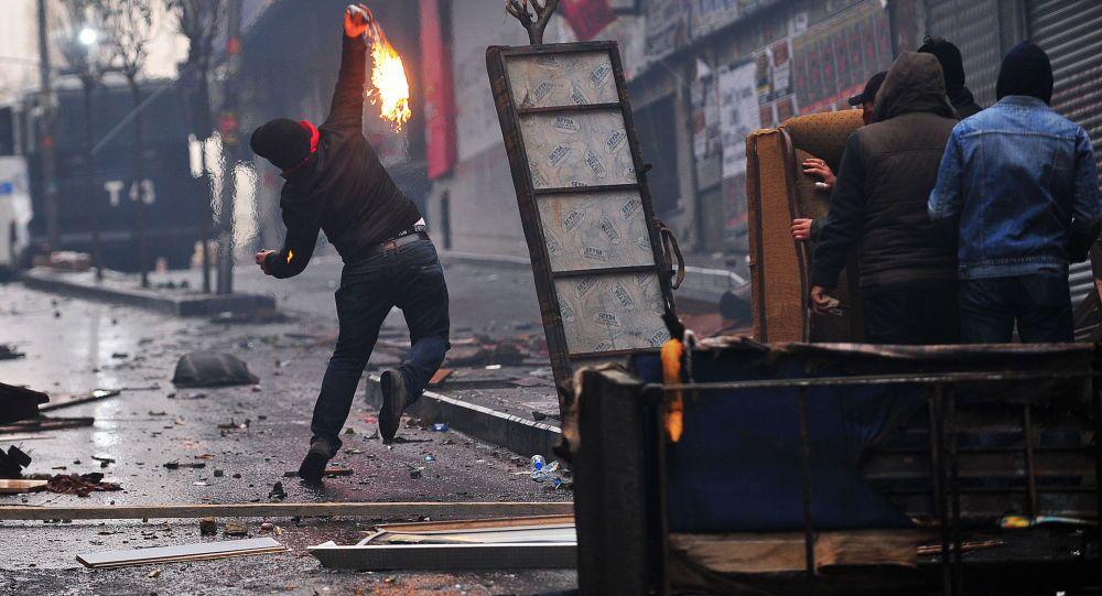 Uomo lancia un Molotov durante gli scontri con le forze dell'ordine