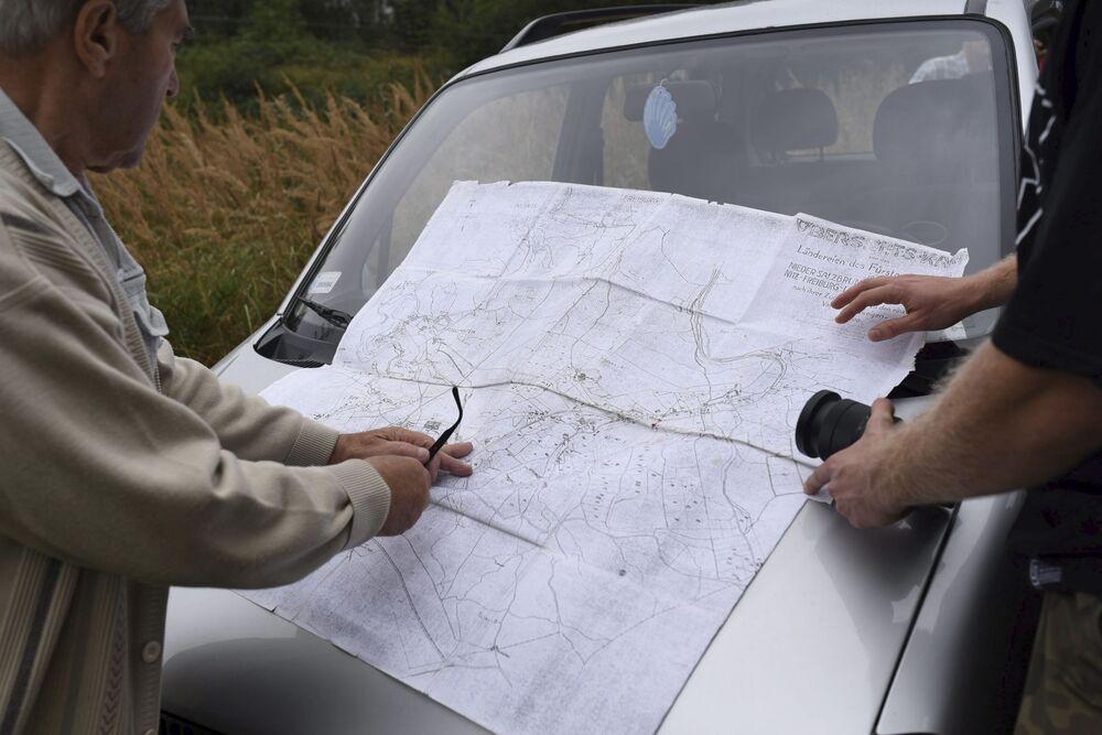 I ricercatori locali con una mappa di località durante le ricerche del treno d'oro nazista nei pressi della città polacca di Wałbrzych.