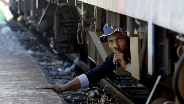 A migrant, hiding under a train, tries to sneak on a train towards Serbia, at the railway station in the southern Macedonian town of Gevgelija, on Monday, Aug. 17, 2015. Over 1,000 migrants from Middle East, Asia and Africa, enter Macedonia daily from Greece, heading north through the Balkans on their way to the more prosperous European Union countries - Sputnik Italia