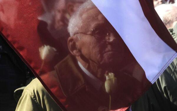 Un manifestante alla marcia in memoria dei Legionari SS a Riga - Sputnik Italia