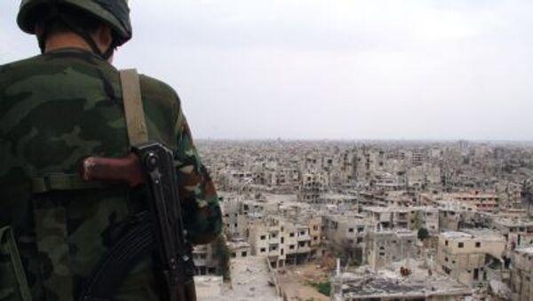 Un soldato siriano sul tetto di un edificio destrutto durante i combattimenti a Homs, Siria - Sputnik Italia