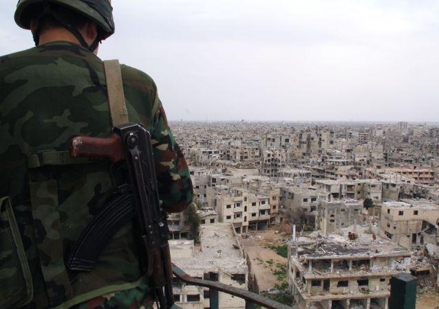 Un soldato siriano sul tetto di un edificio destrutto durante i combattimenti a Homs, Siria