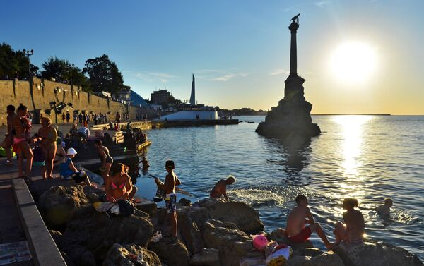 Turisti e residenti fanno il bagno al tramonto di fronte al monumento alle navi affondante nella baia di Sebastopoli. - Sputnik Italia