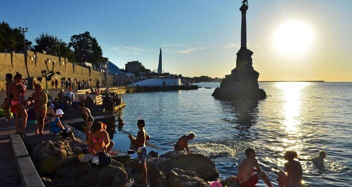 Turisti e residenti fanno il bagno al tramonto di fronte al monumento alle navi affondante nella baia di Sebastopoli.