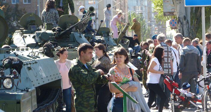 Spettatori parlano con i partecipanti alla parata e guardano i veicoli militari