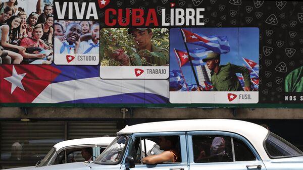 Cuba, scritte che inneggiano alla rivoluzione mentre passa un'auto americana - Sputnik Italia