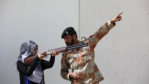 Pakistan Rangers soldier gestures as he instructs a female student of Nadirshaw Eduljee Dinshaw (NED) University during a counter-terrorism training demonstration at the Rangers Shooting & Saddle Club (RSSC) on the outskirts of Karachi, February 24, 2015 - Sputnik Italia