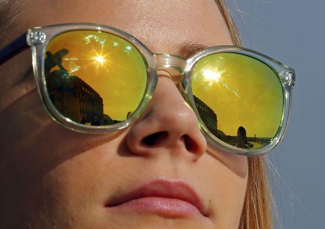 Budapest, una ragazza con gli occhiali da sole osserva l'eclisse.