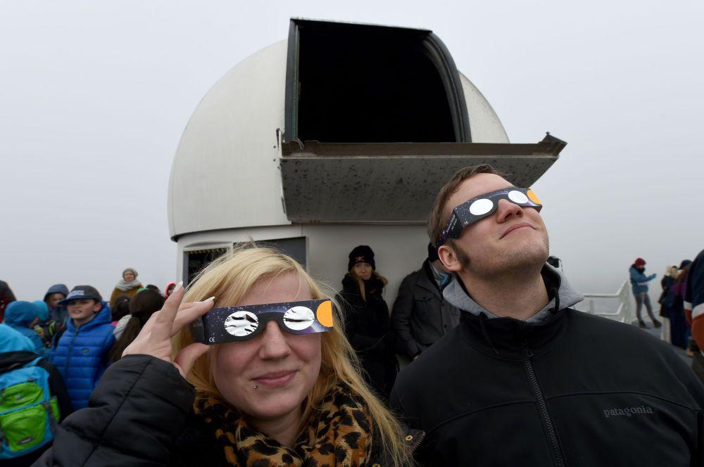 Gli abitanti della città tedesca di Kiel osservano l'eclisse solare.