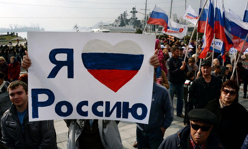 Un abitante di Vladivostok tiene un cartello con la scritta Amo la Russia alle celebrazioni della Giornala dell'unità nazionale.