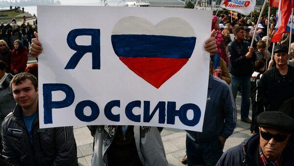 Житель Владивостока держит плакат с надписью Я люблю Россию во время празднования Дня народного единства - Sputnik Italia