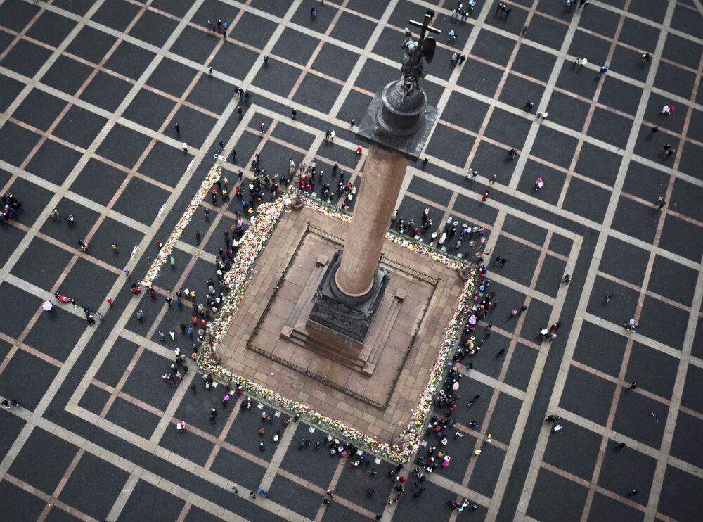 La gente depone i fiori all'imbasamento della Сolonna di Alessandro alla Piazza del Palazzo a San Pietroburgo in memoria delle vittime della sciagura A321.