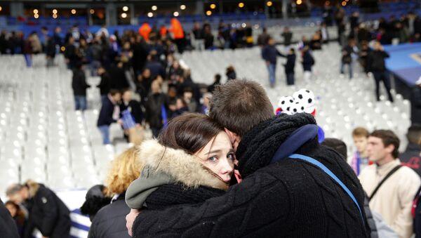 Due spettatori abbracciati e impauriti dopo gli attentati allo Stade de France - Sputnik Italia