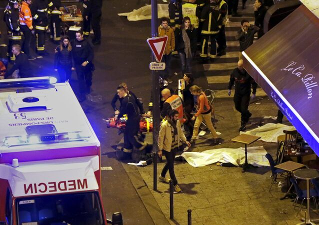 French fire brigade members aid an injured individual near the Bataclan concert hall following fatal shootings in Paris, France, November 13, 2015