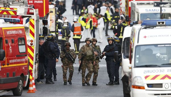 French riot police (CRS), soldiers, firefighters, French red cross members and staff of the emergency medical services in France (SAMU) stand at the scene in Saint-Denis, France, near Paris, November 18, 2015 - Sputnik Italia