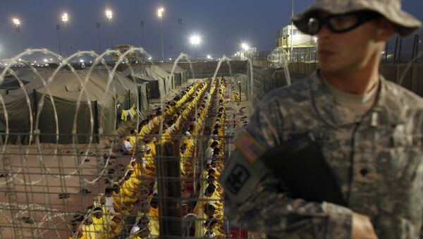A US soldier stands guard as detainees pray at U.S. military detention facility Camp Bucca, Iraq. - Sputnik Italia