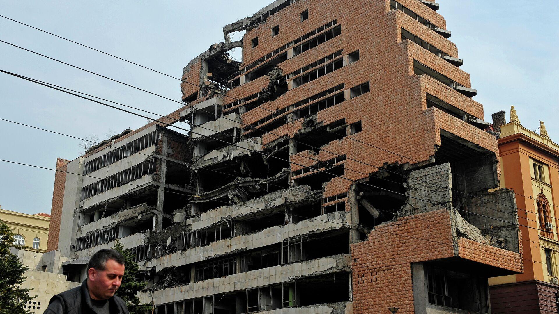 A man walks past the building of former federal military headquarters in Belgrade on March 24, 2010, destroyed during the 1999 NATO air campaign against Yugoslavia. - Sputnik Italia, 1920, 11.06.2021