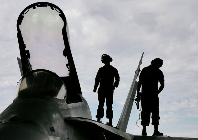 U.S. Marines work atop an F/A-18 at the 309th Aerospace Maintenance and Regeneration Group boneyard in Tucson, Ariz