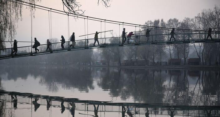 Cittadini nordcoreani attraversano il ponte sopra il fiume Pothong, nel centro della capitale Pyongyang.