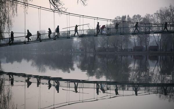 Cittadini nordcoreani attraversano il ponte sopra il fiume Pothong, nel centro della capitale Pyongyang. - Sputnik Italia