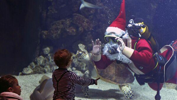 Ребенок наблюдает за драйвером в костюме Санта-Клауса в океанографическом музее Монако  - Sputnik Italia